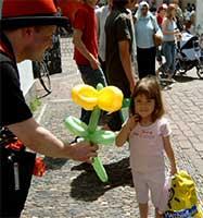 Ballonkünstler mit Ballonblume im Kindergarten beim Kindergartenfest